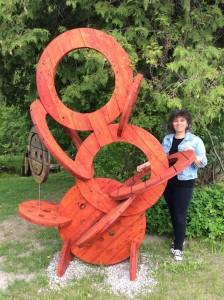 Ginette Robitaille et sa sclupture « Anneaux planétaires » réalisée avec du bois récupéré de bobines de fil électrique, prélevé dans un conteneur à déchets et exposée dans le parc du Ruisseau de la Brasserie, dans le cadre du Festival du Recycl'Art de Gatineau.