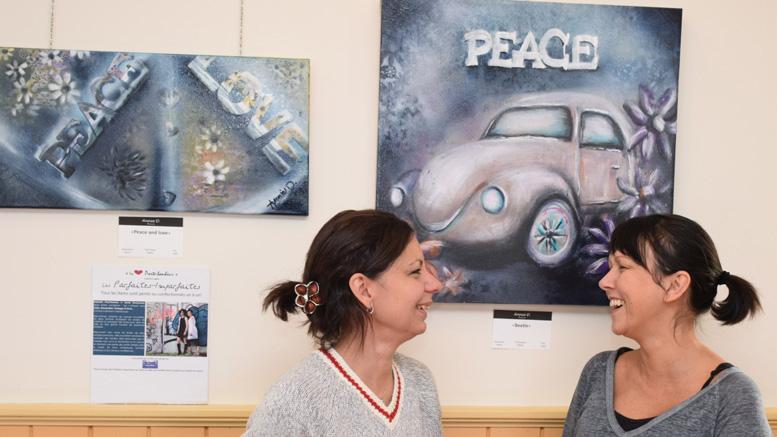 Annie et Nathalie devant une beatel, une toile qu'Annie a peinte évoquant des sentiments de paix et de liberté.