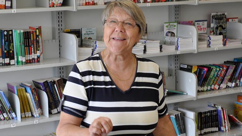 Lucie Papineau, bénévole responsable de la bibliothèque de l'école primaire des Falaises est visiblement heureuse de contribuer à développer le goût de la lecture auprès des jeunes.