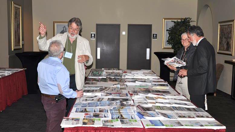 Photo courtoisie; Michel Fortier et Raynald Laflamme (Le Hublot) devant la table des journaux communautaires