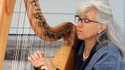 Johanne Fontaine qui, du parvis de l'église, faisait résonner les cordes de sa harpe pour le bonheur des personnes qui s'arrêtaient pour l'écouter. Photo : Jacinthe Laliberté