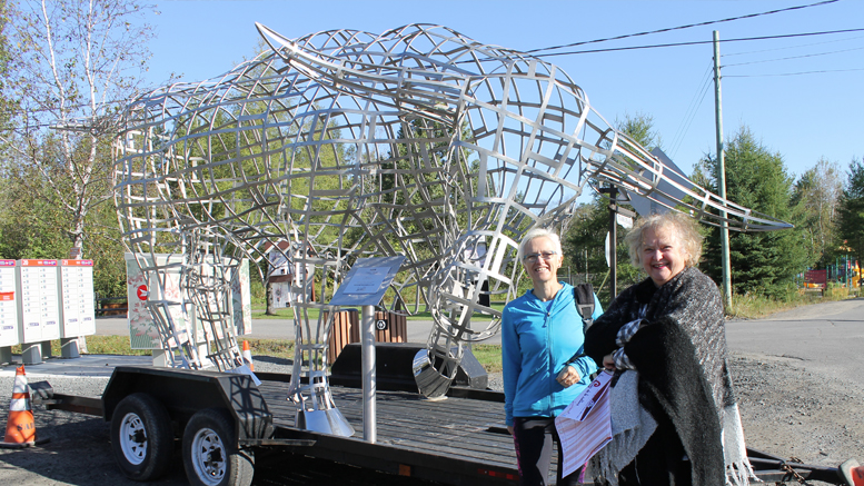 Les deux premières Annelacoises à se lancer sur le circuit culturel posent devant la sculpture de Mathieu Isabel. Photo : Jacinthe Laliberté