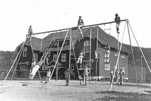 Des jeunes de Boys' farm dans les balançoires devant les «cottages» dougall et birks en 1928 – Photographie avec l'aimable permission du CIUSSS de l'Ouest de l'île de Montréal / Centre de la famille et de la jeunesse Batshaw.